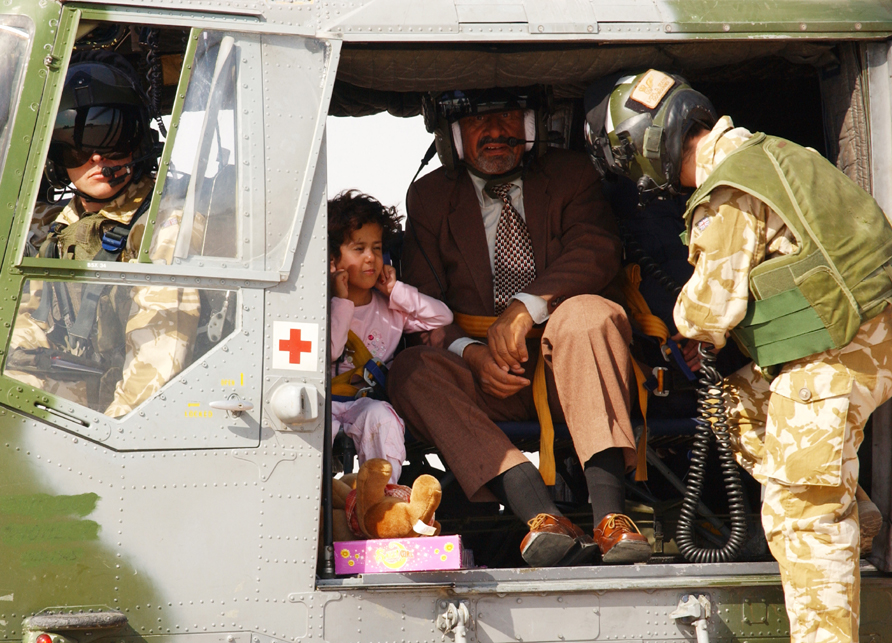 A US Army Soldier assists a seven-year-old Iraqi girl out of a helicopter at the Basra International Airport Sept. 5, 2004. (U.S. Army photo by Staff Sgt. Christopher J. Crawford)